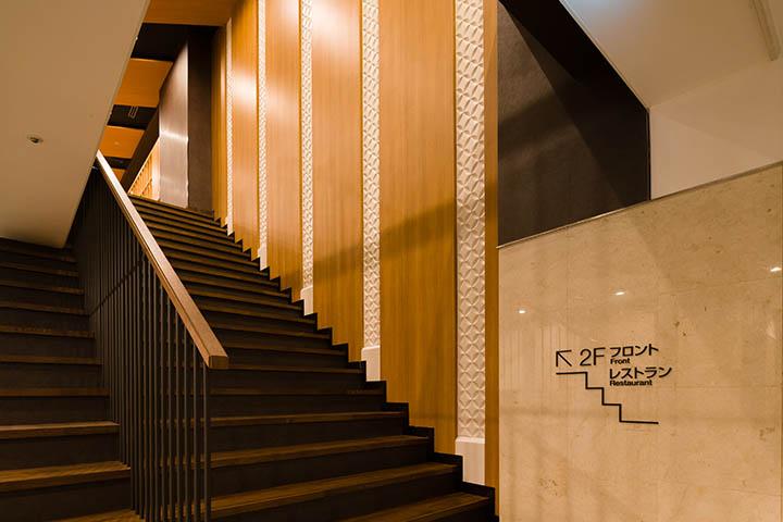 既存オフィスビルのホテルコンバージョンを施した「トーセイホテルココネ上野」ではエントランスホールの階段が、あなたをフロントまで迎え入れます。